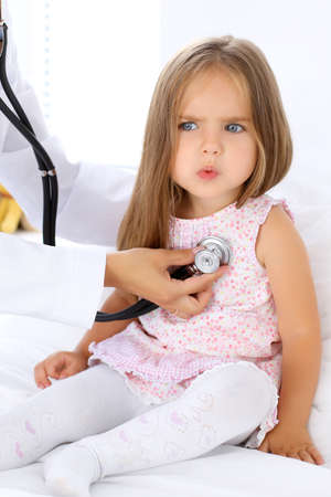 Doctor examining a little girl by stethoscope. Patient is in perplexity Stock Photo