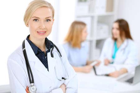 Doctora sonriendo en el fondo con el paciente y su médico en el hospital