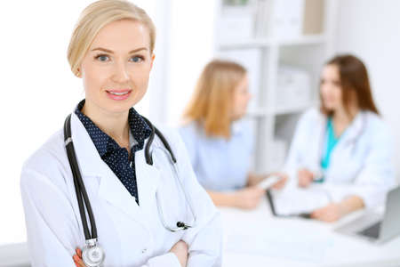 Female doctor smiling on the background with patient and his physician in hospital Stock Photo