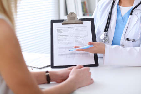 phisician: Close up of a doctor and  patient hands while phisician pointing into medical history form at clipboard