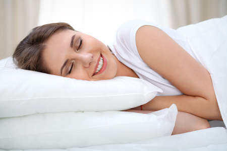 drowsy: Beautiful young and happy woman sleeping while lying in bed comfortably and blissfully smiling Stock Photo