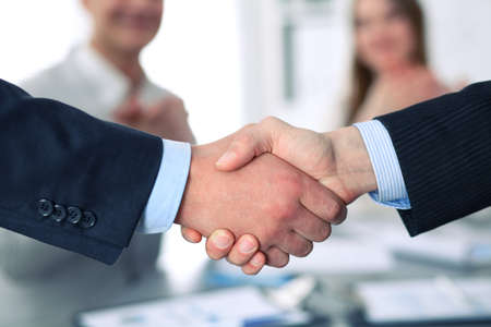 Business handshake at meeting or negotiation in the office. Partners are satisfied because signing contract or financial papers.