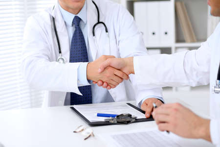 handclasp: Two doctors shaking hands to each other sitting at the table in hospital office Stock Photo