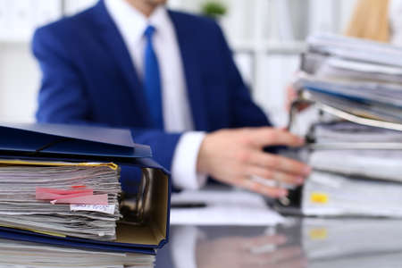 Binders with papers are waiting to be processed with businessman and secretary back in blur. Accounting planning budget, audit, insurance  and business concept Standard-Bild