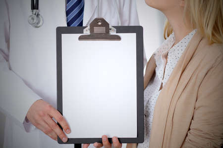 oncologist: Doctor and patient holding clipboard free copy space. Medical ethics and trust concept. Stock Photo