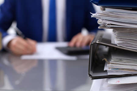 Binders with papers are waiting to be processed with businessman back in blur. Accounting planning budget, audit, insurance  and business concept
