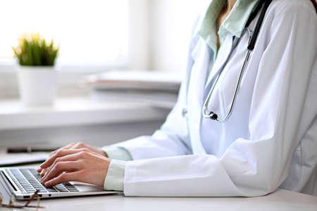 Primo piano di sconosciuto medico femminile seduto al tavolo vicino alla finestra in ospedale e digitando al computer portatile Archivio Fotografico - 80405331