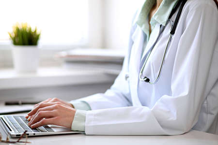 Close up of  unknown female doctor sitting  at the table near the window in hospital and typing at laptop computer Standard-Bild