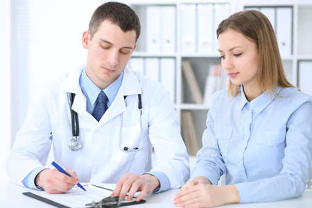 Male doctor  and  female patient sitting at the table in medical cabinet Stock Photo