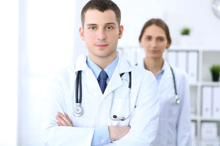 Friendly male doctor on the background of female physician in hospital office