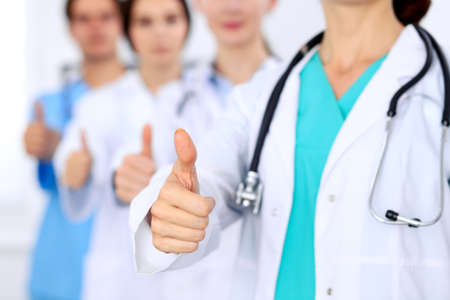Group of doctors showing OK or approval sign with thumb up. High level and quality medical service, best treatment and patient care concept Stock Photo