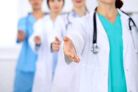 physiotherapists: Group of doctors offering helping hand in hospital closeup. Friendly and cheerful gesture. Medical cure and tests advertisement concept. Physicians ready to examine and save patient