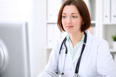 Young brunette female doctor sitting at a desk and working on the computer at the hospital office.  Health care, insurance and help concept. Physician ready to examine patient Stock Photo