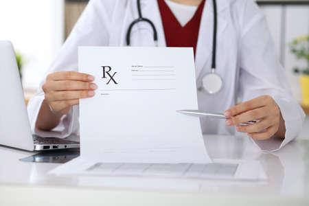 Vrouwelijke geneeskunde arts hand houden klembord pad en voorschrift geven aan de patiënt close-up. Panacea en levensredding, voorschrijven behandeling, legale drugstore, contraceptie concept Stockfoto - 80422017