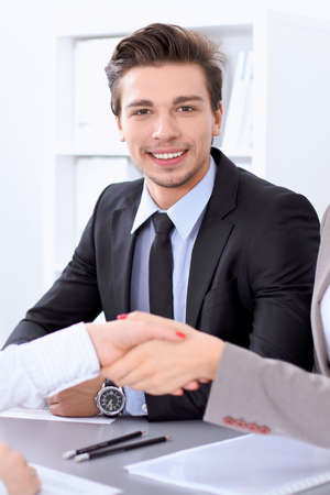Businessman looking at camera while partners shaking hands at meeting