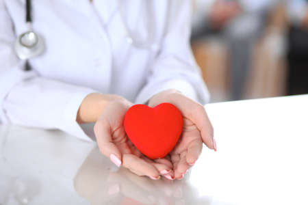 Female doctor with stethoscope holding heart.  Patients couple sitting in the background