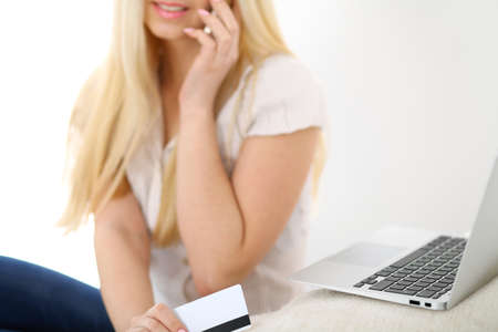 cross legged: Happy woman doing online shopping at home . Close- up of a hand holding a credit card next to a laptop Stock Photo