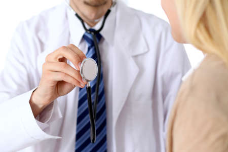oncologist: A doctor with a stethoscope in his hand next to his patient . The therapist is ready to examine a patient.