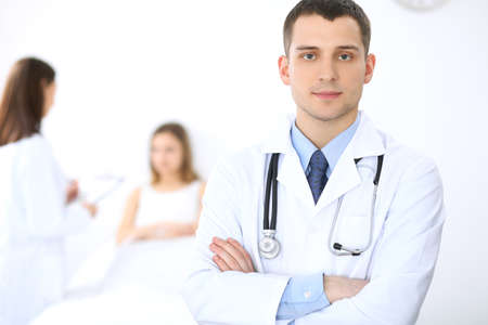 Friendly male doctor on the background with patient in the bed and his physician