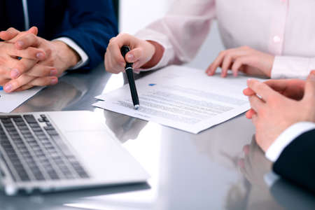 Group of business people and lawyers discussing contract papers Banque d'images