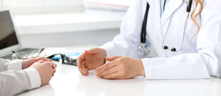 Doctor and patient sitting at the desk. Medicine and health care concept