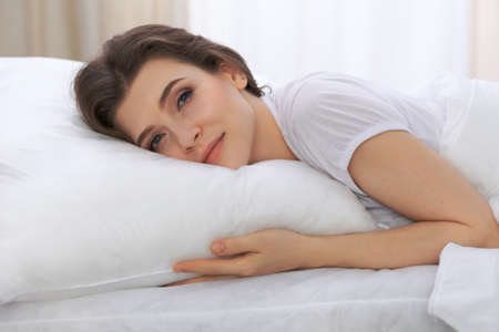 drowsy: Beautiful young woman sleeping while lying in her bed and relaxing comfortably. It is easy to wake up for work or the day off. Concept of pleasant and rest reinstatement for active life
