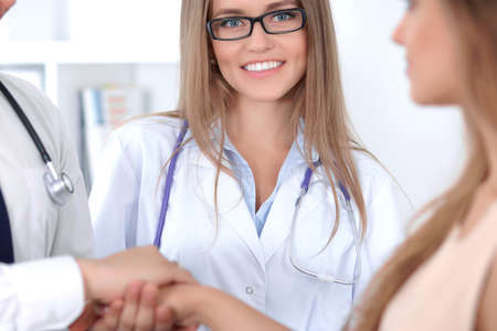 hospital patient: Friendly male doctor and female patient shaking hands. Stock Photo