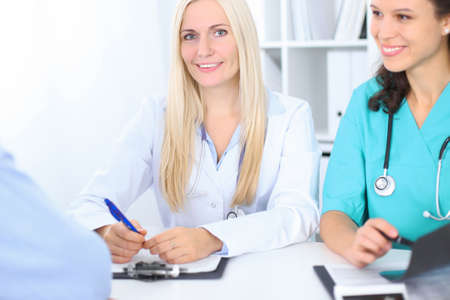 hospital patient: Two confident friendly female doctors sitting at the table and listen to patient . Focus on blonde female doctor. Medical and health care concept