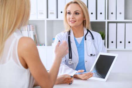 Doctor y paciente discutiendo algo mientras phisician apuntando en la computadora portátil Foto de archivo