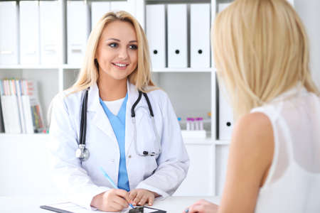 hospital patient: Doctor and  patient  discussing something while sitting at the table . Medicine and health care concept Stock Photo