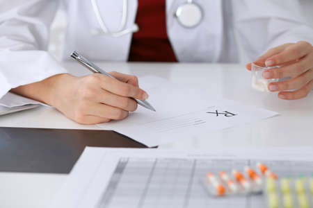prescription pad: Female medicine doctor fills up prescription form to patient closeup. Panacea and life save, prescribe treatment, legal drug store, contraception concept. Stock Photo