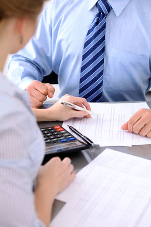 Bookkeepers or financial inspector making report, calculating or checking balance. Audit concept Фото со стока