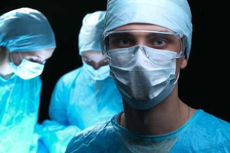 theatre masks: Three surgeons at work operating in surgical theater saving patient and looking at life monitor. Resuscitation medicine team wearing protective masks. Surgery and emergency concept