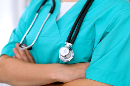 Female surgeon doctor is standing with arms crossed at hospital. Physician is ready to examine patient.