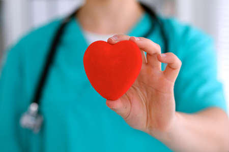 hospital patient: Female surgeon doctor with stethoscope holding heart. Stock Photo
