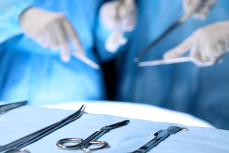 Surgical tools lying on the table while group of surgeons at background operating patient. Steel medical instruments ready to be used Stockfoto