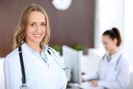 Beautiful young smiling female doctor standing in a hospital with her colleague in the background