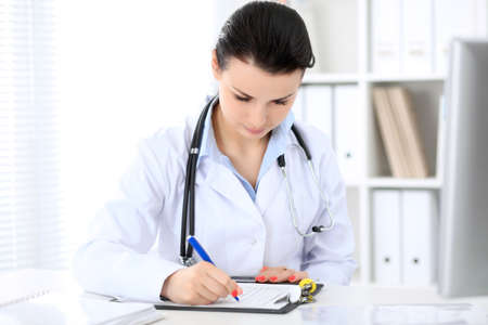 Young brunette female doctor sitting  with clipboard near window in  hospital and filling up medical history form.