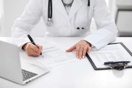 oncologist: Close-up of a female doctor filling out application form , sitting at the table in the hospital. Stock Photo