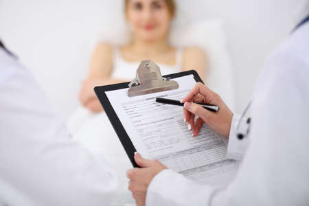 oncologist: Close-up of a female doctor holding application form while consulting patient.