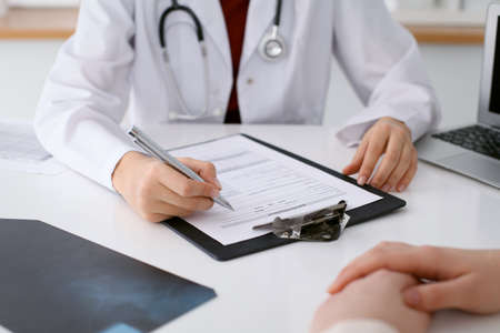 oncologist: Close up of a female doctor filling up  an application form while consulting patient
