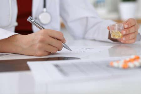 Vrouwelijke geneeskunde arts vult op voorschrift formulier op naar de patiënt close-up. Panacea en levensredding, voorschrijven behandeling, legale drugstore, contraceptie concept Stockfoto