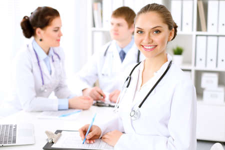 Happy doctor woman  with medical staff at the hospital sitting at the table Stock Photo