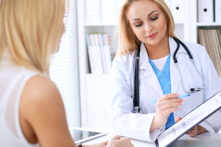 Doctor and  patient  discussing something while phisician pointing into medical history form at clipboard. Medicine and health care concept Stock Photo