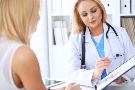 Doctor y paciente que discuten algo mientras que phisician que señala en forma de la historia médica en el tablero. Medicina y concepto de cuidado de la salud
