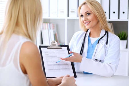 phisician: Doctor and  patient  discussing something while phisician pointing into medical history form at clipboard