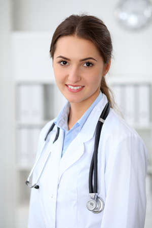 Young brunette female doctor standing with arms crossed and smiling at hospital.  Physician ready to examine patient