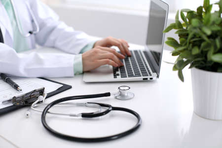 oncologist: Close-up of stethoscope is lying on the table near female doctor typing on laptop computer Stock Photo