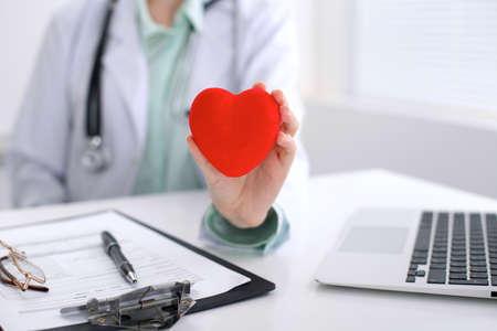 Female doctor with stethoscope holding heart.   Cardio therapeutist, physician make cardiac physical, heart rate measure, arrhythmia, old age life concept