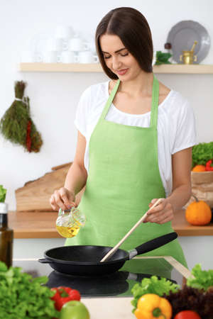 latinamerican: Beautiful Hispanic woman is cooking in the kitchen Stock Photo